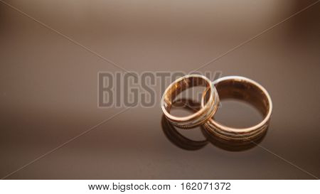 Golden wedding rings on mirror glasses table - one lies on top of another close up