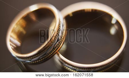 Golden wedding rings on mirror glasses table - one lies on top of another, macrom, horizontal, close up