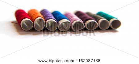 Colorful spools of thread on a white background. Colored thread for sewing