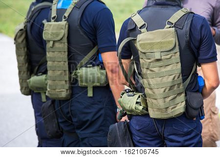 law enforcement with tactical hydration pack and tactical equipment in field training course