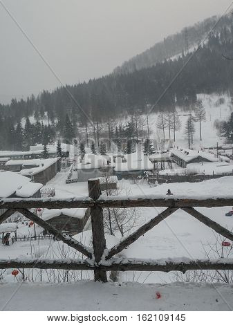 Village with thatched roof houses covered in snow