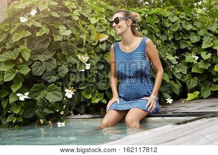 Stylish Happy Young Pregnant Woman In Dark Shades Relaxing Outdoors At Swimming Pool, Her Legs Dangl