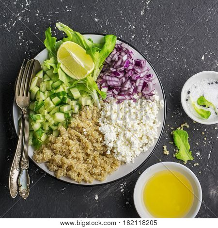 Ingredients for a light salad of quinoa, cucumber, cheese and sweet red onion with butter and lettuce on a light gray background. Top view