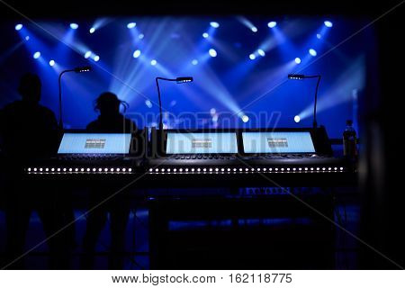 sound mixer console with concert background under blue floodlights. Copy space for advertising text.