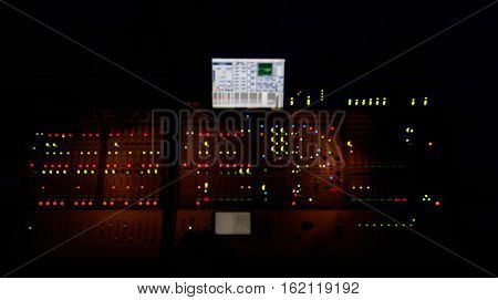 Blurred sound mixer with many red and green lights. Soundman table.