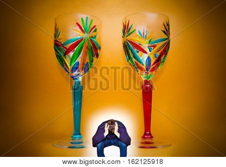 Portrait of two wineglasses and depressed man. Concept of youth addicted to alcohol alcoholism social problem