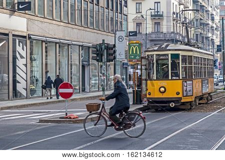 MILAN ITALY - DECEMBER 11 2016:Old yellow tram with passengers and senior man bicyclist on the street in Milan. A symbol of the city traditional ATM Class 1500 is a series of trams used from 1927.