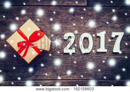Wooden Numbers Forming The Number 2017, For The New Year And Snow On Rustic Wooden With Gift Box And