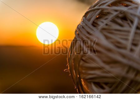 Ball of thread ulluminated by the rays of sunset. Twisted thread of fate
