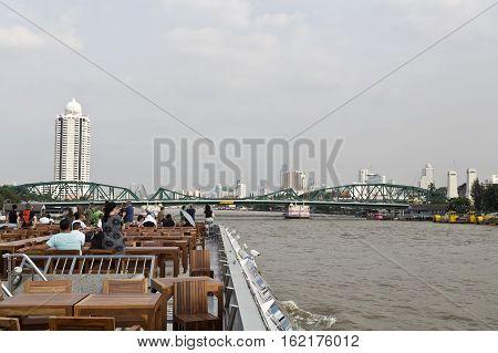 BANGKOK, THAILAND - November 4, 2016: People on board of a cruise boat approching the Phra Phuttayotfa Bridge or the Memorial Bridge a bascule bridge over the Chao Phraya River in Bangkok Thailand.