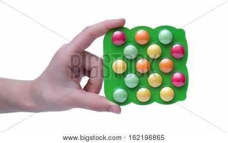 Child's Hand Holding Colorful Pills For Kids In The Plastic Packaging Isolated On White Background.