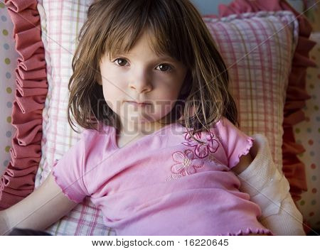 Young child laying in bed with fractured elbow and arm.