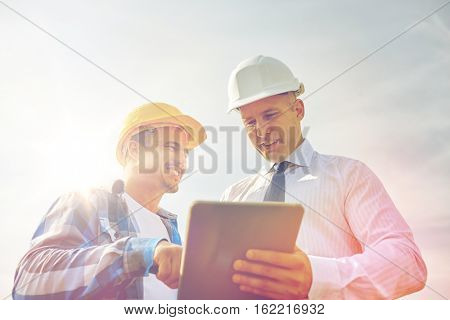 business, building, teamwork, technology and people concept - smiling builders in hardhats with tablet pc computer outdoors