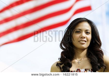 Beautiful Asian American Woman with the stripes of the American flag behind her.