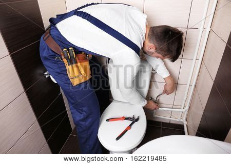 Plumber fixing water hose on toilet cistern