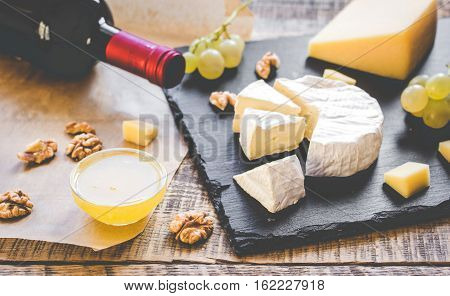 bottle of red wine, appetizers and corkscrew on wooden background.