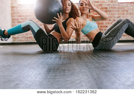Two young women exercising with medicine ball in gym. Girls working out in gym.