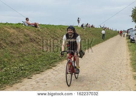 QUIEVYFRANCE- JUL 07: Unidentified amateur cyclist riding on a cobblestone road before the apparition of the peloton during the stage 4 of Tour de France in Quievy France on 07 July2015.