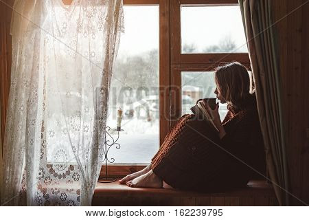 Pre teen child in warm woolen sweater seating on window sill and drinking tea. Winter weekends in old log house. Cold snowy weather. Cozy homely concept.