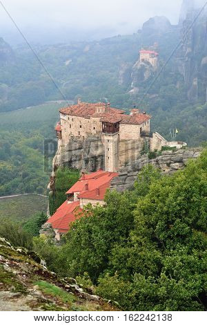 View from above on the Meteora landscape and Holy Monastery Roussanov at sunrise Monastery of St Nikolaos Anapafsas on background Meteora Greece