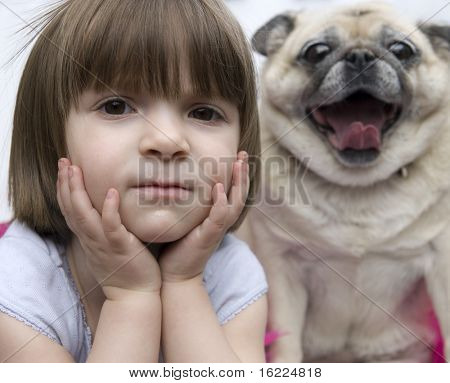 A lovely adorable young child with serious  look hands on face with pug dog yawning.