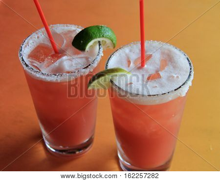 Two alcoholic beverages with the fruity flavors of cranberry,orange, and mango, with salt on rims of chilled glasses.