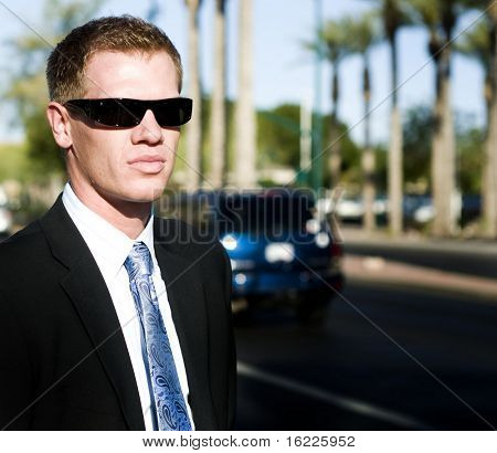 Handsome man wearing black suit with dark shades