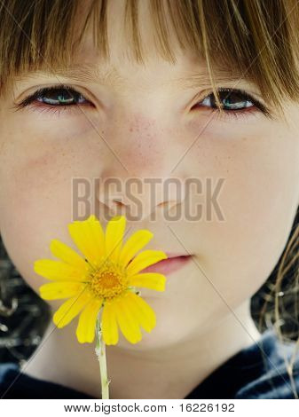 Young child holding yellow flower to her face
