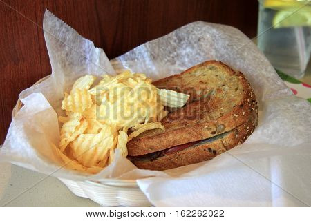 Simple plate with paper napkin, with toasted cheese,tomato and bacon sandwich with a side of potato chips for lunch.