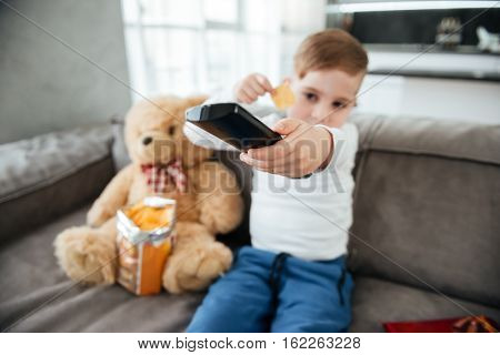 Image of boy sitting on sofa with teddy bear at home and watching TV while eating chips. Holding remote control. Focus on remote control.