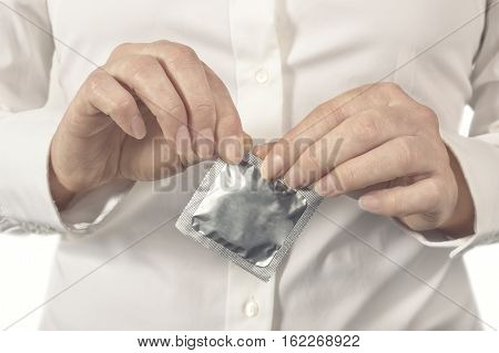 Female hands opening a new condom. Healthcare and medicine concept