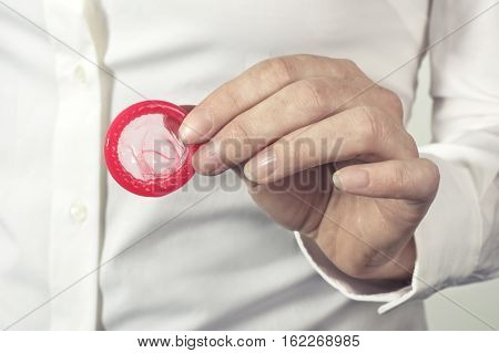 Red condom in hand for safe sex. Healthcare and medicine concept.