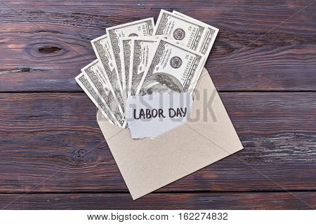Dollars in envelope and card. Money near Labor Day card. Always a valuable gift.