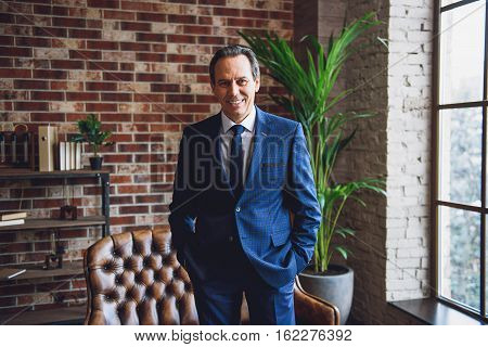 Well dressed mature businessman is laughing in spacious room. He has his hands in pockets and looking directly at camera