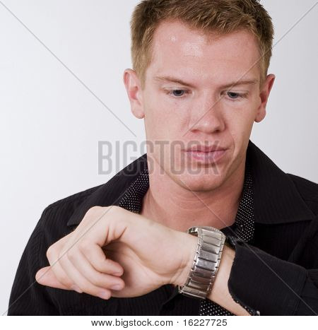Man looking at his watch with annoyed look on he face.