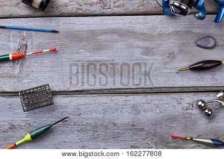 Fishing tackle on wooden background. Equipment for catching fish. Fishing as a hobby.