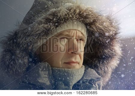 The guy's portrait in a winter jacket a fur hood in the winter a knitted cap a scarf and gloves in the winter