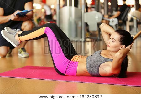 Young athletic woman doing crunches in gym