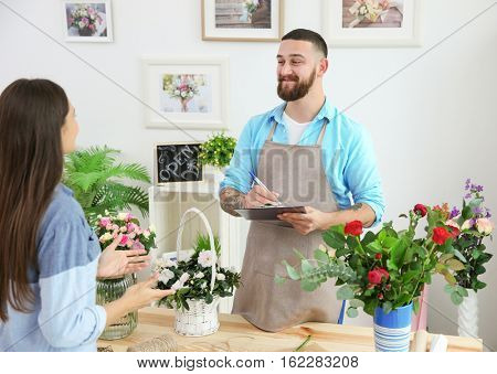Handsome florist accepting order of young woman