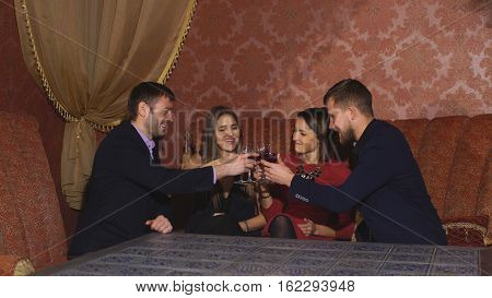 Two amorous couples celebrating together at restaurant, Two happy smiling young couples with champagne at celebration