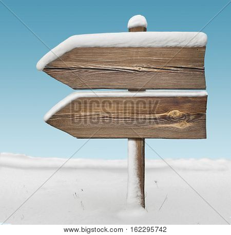 Wooden direction sign with less snow on it and with sky on background. two arrows in one direction