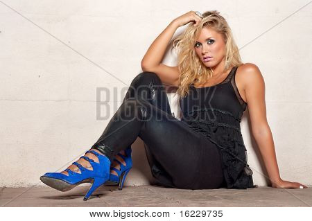 Fashion concept image of beautiful club party girl sitting on sidewalk on a hot summers night.