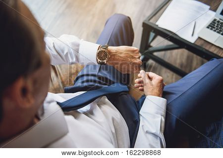 Mature male businessperson is sitting and checking time. Top view