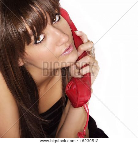 Close up studio photo of beautiful young woman listening and talking on red old fashioned style phone.  Isolated.