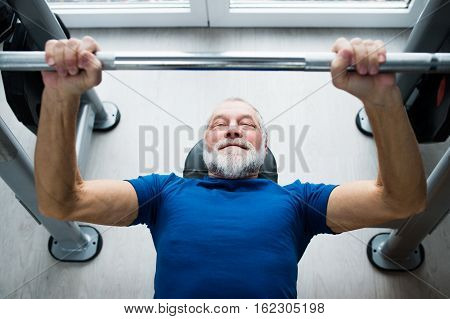 Senior man in sports clothing in gym working out with weights, bench pressing.