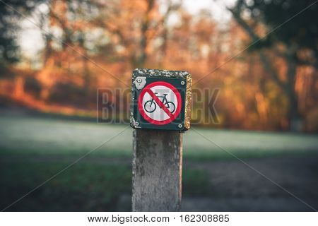 Bike restriction sign in a park in autumn with no bike riding allowed
