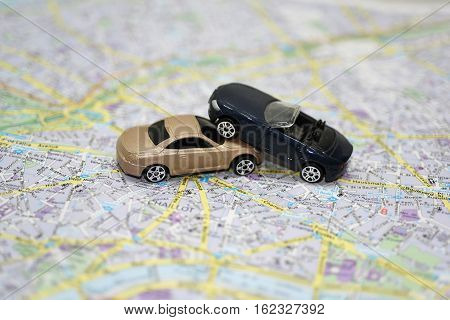Abstract composition on the road accident. Paper map with small toy cars.