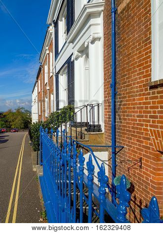 white houses and houses of red brick on Beacon Street. Blue fence. Sunny day. Exmouth. Devon. UK