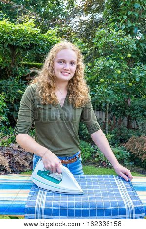 Young european woman ironing tea towel with iron outdoors