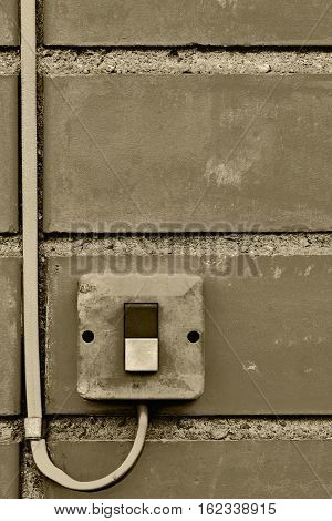 Outdoor electric equipment control industrial button switch wire cable closeup, old aged weathered grungy brick wall background texture pattern, large vertical textured grunge copy space sepia